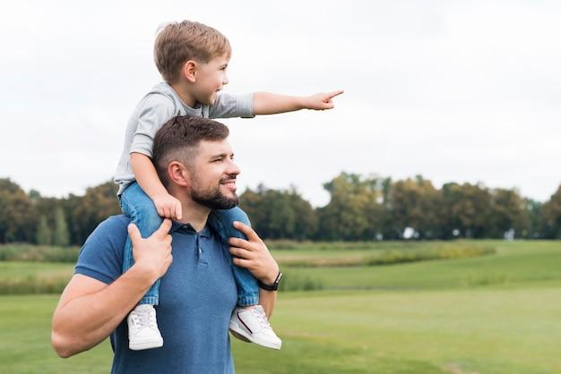 Vader houdt zijn zoon op zijn schouders zijaanzicht