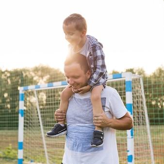 Vader houdt zijn zoon op zijn schouders