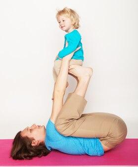 Vader houdt zijn zoontje op zijn voeten, yoga, gelukkig gezin