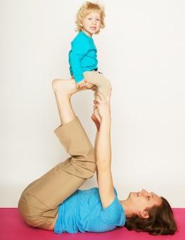 Vader houdt zijn zoontje op zijn voeten, yoga, gelukkige familie