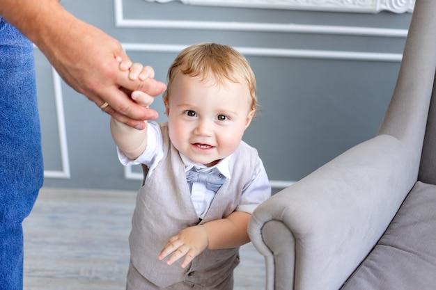 Vader houdt zoontje van 1 jaar oud bij de hand, familiedag, vaderdag