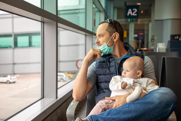 Vader in medisch masker en zijn dochter die op het vliegtuig op de luchthaven wachten