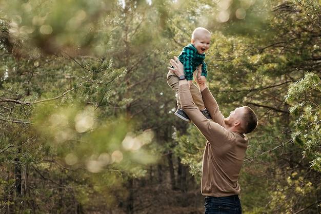 Vader is aan het rommelen met zijn zoon. vader gooit zijn zoon in de lucht, vader speelt met zijn zoon. blij kind. vaderdag.