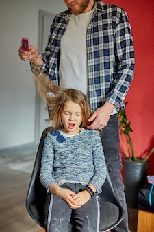 Vader kamt, borstelt het haar van zijn dochter thuis, kind trekt gezichten over haren trekken