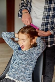 Vader kamt, het haar van zijn dochter thuis borstelt, kind dat gezichten trekt over het trekken van haar