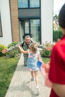 Vader keert terug naar huis. gelukkige vader keert na een half jaar dienst terug naar zijn vrouw en dochter