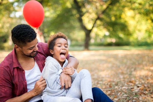Vader kietelt zijn dochter terwijl ze geniet en lacht in zijn omhelzing