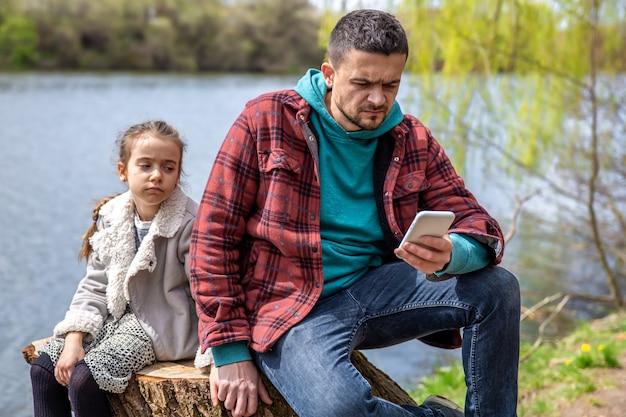 Vader kijkt op zijn telefoon en let niet op zijn dochter, voor een wandeling door het bos.