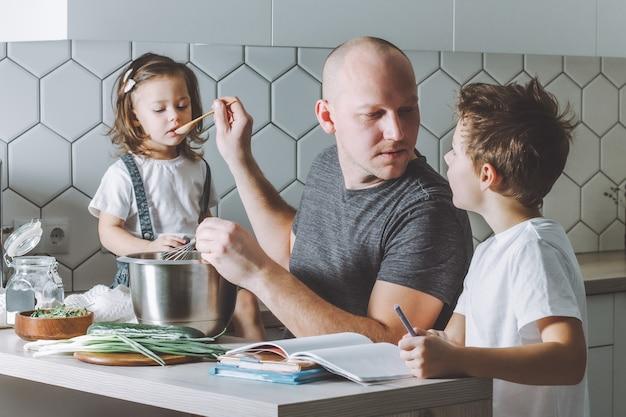 Vader klopt omelet met garde, helpt zijn zoon met zijn huiswerk en geeft zijn dochter te eten in de keuken