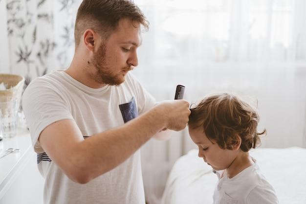 Vader knipt het haar van haar zoon in de kamer. familie tijdens quarantaine