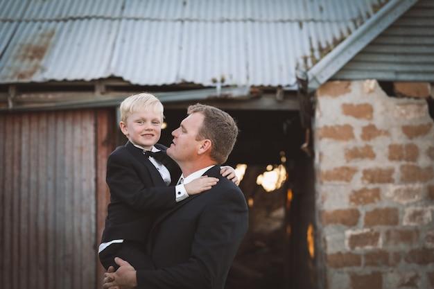 Vader knuffelt zijn zoon in formele kleding voor een speciale gelegenheid