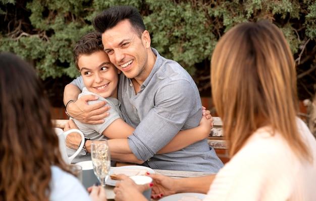 Vader knuffelt zijn zoon terwijl hij buiten luncht met het gezin