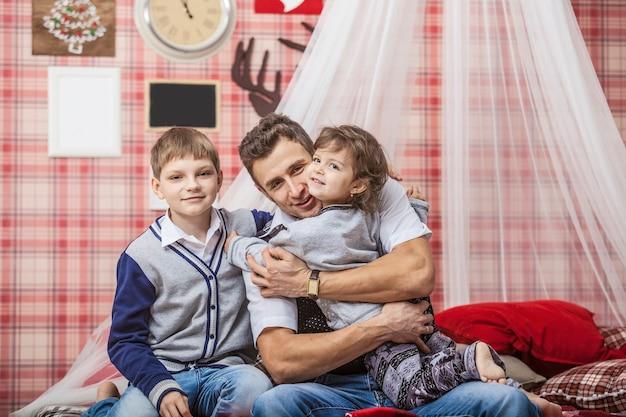 Vader knuffelt zoon en dochter de kinderen thuis in een comfortabele omgeving