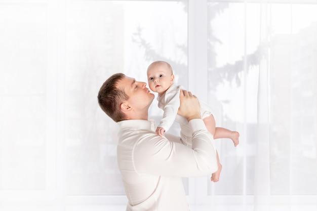 Vader kust pasgeboren baby thuis bij het raam