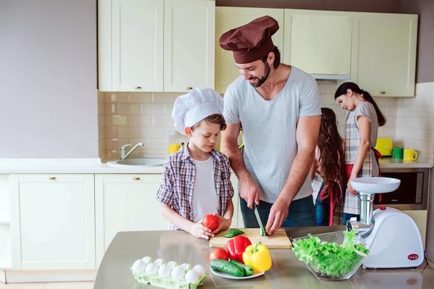 Vader laat zijn zoon zien hoe hij groenten moet snijden.