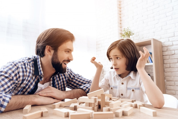 Vader lacht om het feit dat zoon toren jenga is ingestort.