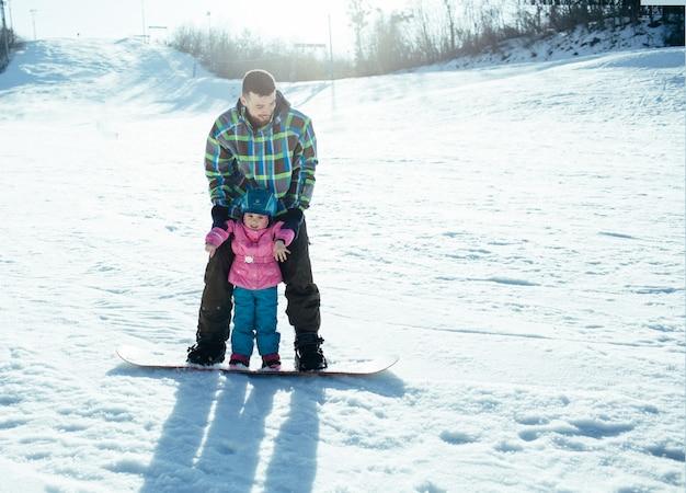 Vader leert dochter hoe te rijden op snowboard. veel plezier samen staan op snowboard. wintervakantie in berg tijdens zonnige dag. gemalen vol met witte sneeuw.