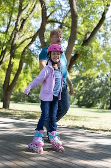 Vader leert dochter rolschaatsen in het park