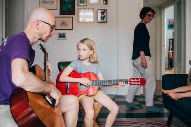 Vader leert zijn dochter gitaar spelen