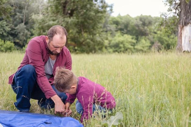 Vader leert zijn zoon een tent opzetten. jongen houdt een touw met belangstelling vast terwijl hij op gras knielt. hoge kwaliteit foto