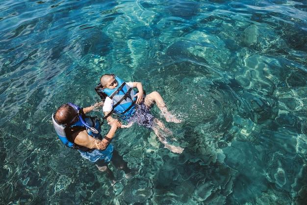 Vader leert zijn zoon zwemmen in de oceaan met een reddingsvest voor de veiligheid