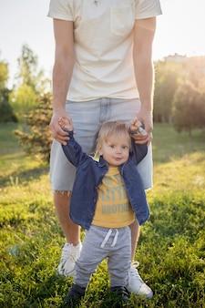 Vader leert zijn zoontje lopen, familie loopt in het park, vader houdt de handen van het kind vast en helpt om te lopen, avondwandeling, vader-zoonrelatie, vertrouwen in de familie, mooie baby