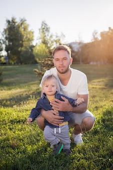 Vader leert zijn zoontje lopen, familiewandelingen in het park, vader houdt de handen van het kind vast en helpt bij het lopen, avondwandeling, vader-zoonrelatie, vertrouwen in het gezin, mooie baby