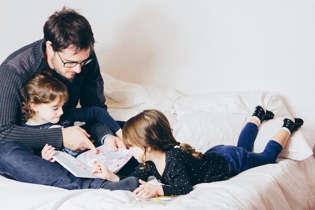 Vader leesboek met schattige meisjes