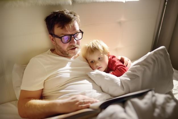 Vader lezen verhaaltjes voor het slapengaan aan kind. papa brengt zoon in slaap