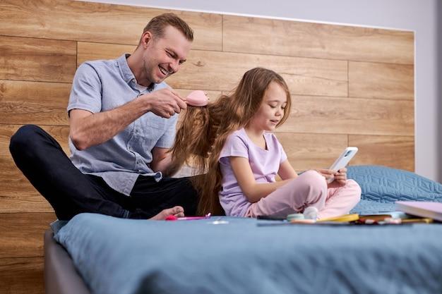 Vader maakt kapsel voor zijn dochter met behulp van kam thuis op bed, knappe blanke man zit zorgzaam haar kind meisje.