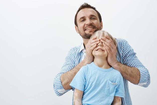 Vader maakt verrassing voor zoon op verjaardag. portret van zorgzame liefhebbende vader die kindogen bedekt met handpalmen en breed lacht