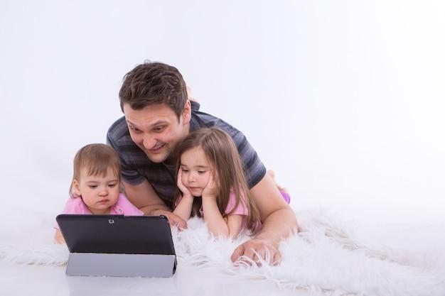 Vader met de kinderen kijkt naar tekenfilms op de tablet. thuisonderwijs voor meisjes tijdens quarantaine. geïsoleerde vaderdag
