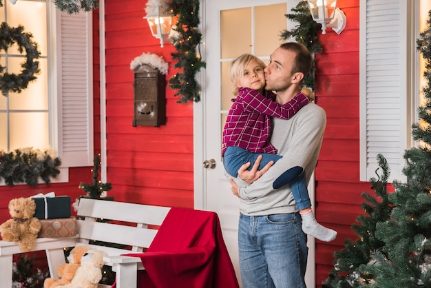 Vader met dochter bij kerstmis voor huis