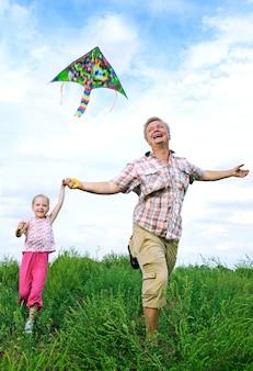 Vader met dochter in de zomer spelen met vlieger