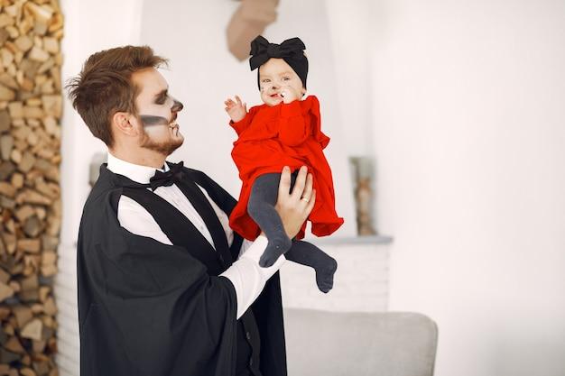 Vader met dochter in kostuums en make-up. familie bereidt zich voor op de viering van halloween.
