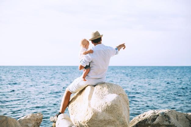 Vader met dochter op zee- en luchtachtergronden man en baby wijzen naar voren