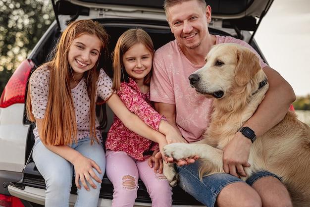 Vader met dochters en golden retriever zittend in de kofferbak van de auto op aard