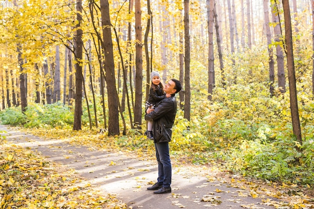 Vader met dochtertje in zijn armen in herfst park