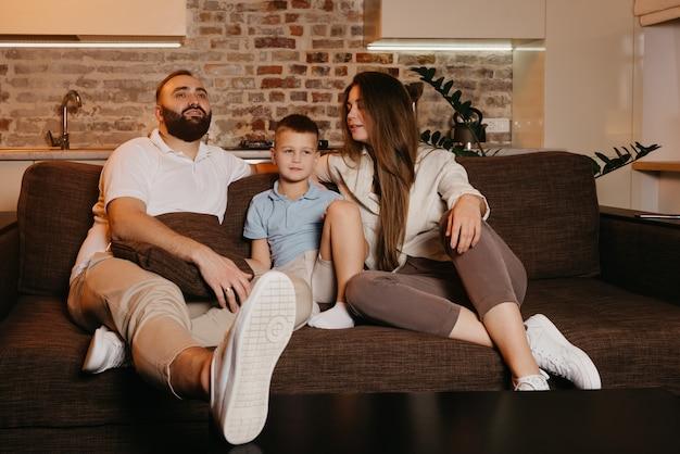 Vader met een baard, zoon en jonge moeder met lang haar kijken tv en glimlachen op de bank