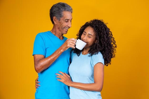 Vader met een kopje koffie langs de neus van zijn dochter zodat ze de geur kan ruiken. foto voor koffie en vaderdagacties