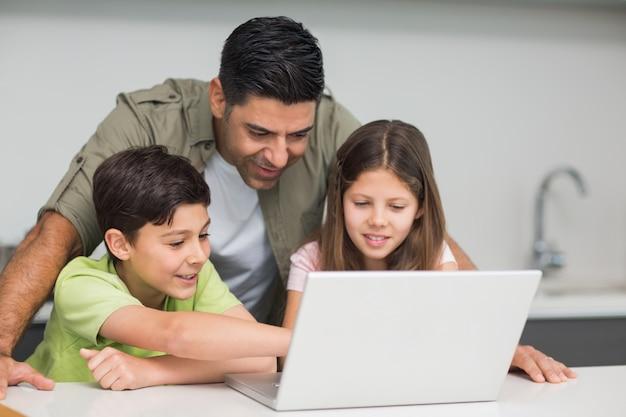 Vader met jonge kinderen met behulp van laptop in de keuken