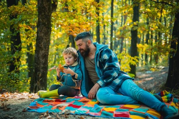 Vader met jonge zoon in de herfstpark. vader en zoon in truien in het park. gelukkige familie, vader en zoontje spelen en lachen op herfstwandeling.