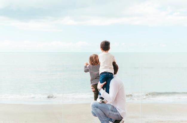 Vader met jongens die op zee kijken