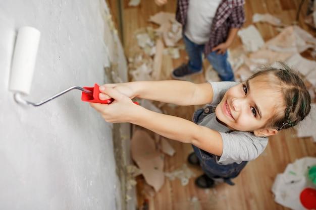 Vader met kind kamer samen repareren en samen de muur schilderen
