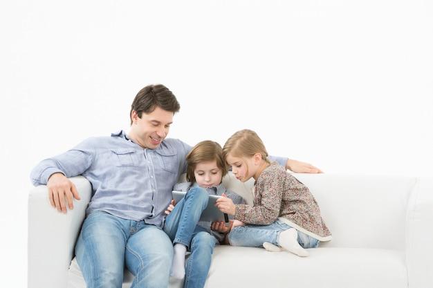 Vader met kinderen die touchpad thuis spelen. thuisonderwijs.