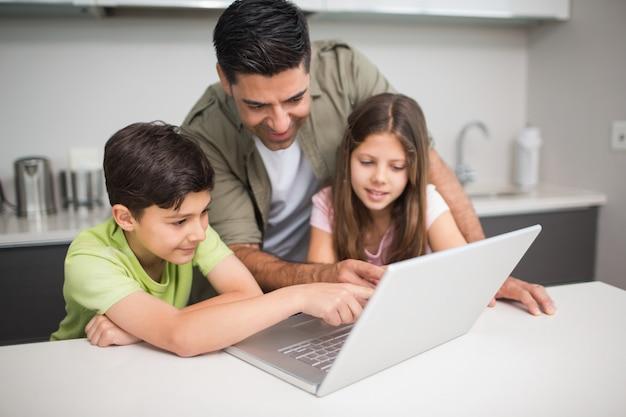 Vader met kinderen met behulp van laptop in de keuken