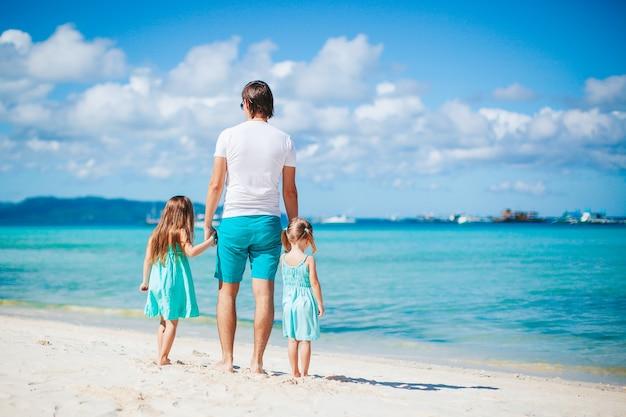 Vader met kinderen op het strand genieten van de zomer. familie vakantie