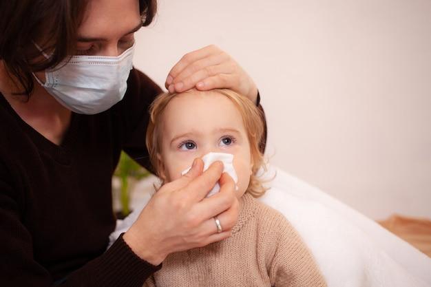 Vader met masker veegt de neus van zijn dochter af. het snot van het kind, lege ruimte voor tekst. verkoudheid, griep, thuisquarantaine, ziek kind.
