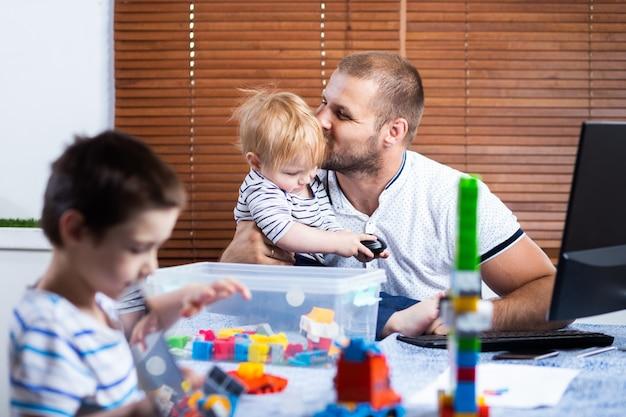 Vader met twee kleine jongens op zijn knieën probeert thuis te lachen. jonge man zorgt voor kinderen en werkt op een computer.