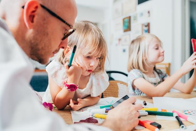 Vader met twee vrouwelijke kinderen tekenen samen